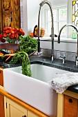 Frisches Gemüse & Blumen neben Spülbecken mit moderner Armatur in ländlicher Bauernküche