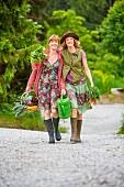 Zwei Frauen tragen Gemüse auf einer Waldstrasse