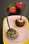 Chocolate-coated apples on sticks, one with sugar sprinkles