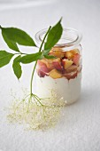 Peach with elderflower yoghurt in a jar with a sprig on edlerflowers