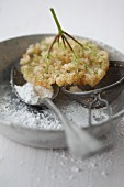 Deep-fried elder flowers on a spoon and a tea strainer dusted with icing sugar