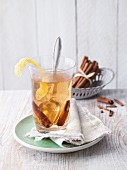 Mate tea punch with lemon zest and cinnamon sticks