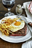 Beef steak with fried egg and potato straw