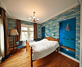 Doppelbett mit Holzrahmen vor tapezierter Wand, seitlich Wandnischen blau gestrichen und eingespannte Ablagen