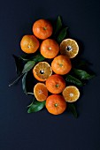 Mandarins and mandarin leaves on a blue surface