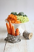 Carrots in a paper bag with a pile of grated vegetables in the background