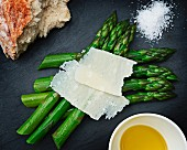Green asparagus with shaved cheese, melted butter, sea salt and bread (seen from above)