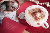 Tasse Kaffee mit Milchschaum daneben Einladungskarte & Gebäckteller