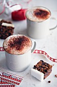 Coffee with milk foam and cocoa powder served with Christmas cake