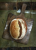 A loaf of country bread on a chopping board (seen from above)
