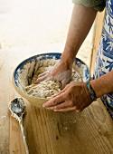 A person kneading a bowl of dough