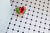 A watermelon on the floor of a kitchen