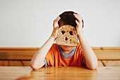 A boy sitting at a table with a slice of toast in front of his face