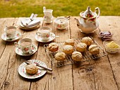 Teatime in a garden with tea and scones on a wooden table