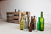Various empty bottles in front of a wooden crate in a garage