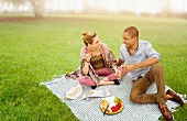 Pärchen macht Picknick auf Wiese im Park