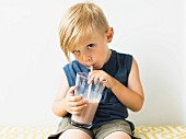 A little boy drinking a milkshake from a glass with a straw