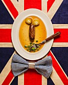 A face made from a sausage and vegetables on a Union Jack flag