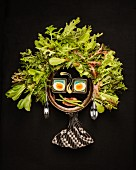 A woman's face made from lettuce leaves, hard-boiled eggs and asparagus
