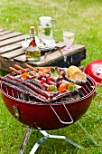Sausages and vegetables on a charcoal barbecue