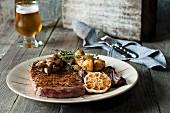 Ribeye Steak vom Grill mit roten Zwiebeln, Knoblauch, Pilzen und Thymian-Kartoffeln