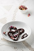 Chocolate hearts with dried rose petals on a plate