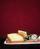 Various types of cheese and rosemary on a chopping board