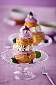 Religieuse with purple icing and cream flowers
