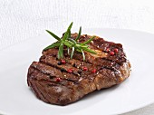Beef ribeye steak with peppercorns and rosemary