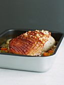 Crispy roast pork with vegetables in a roasting tin