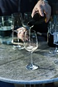 A wine tasting session: white wine being poured into a glass