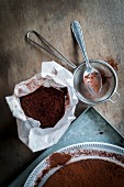 Chocolate cake on a metal tray with utensils for sprinkling cocoa powder on a wooden table