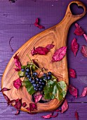 Grapes and autumnal leaves on a wooden board