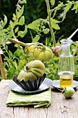 Green tomatoes on a vine and tomato with a bottle of olive oil on a rustic wooden board