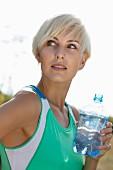 Junge blonde Frau in Sportkleidung mit Wasserflasche