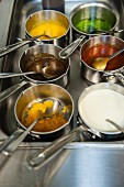 Various sauces in pots in a restaurant kitchen