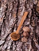 Muskat, ganz und gemahlen, mit Holzlöffel auf Baumrinde