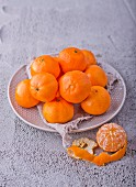 Mandarins on a plate, one peeled