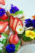 Bread with rocket pesto, strawberries and spring flowers