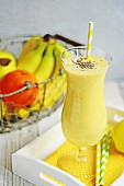 A smoothie made with orange, bananas, apples and chia seeds