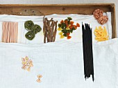 Colourful types of pasta on a linen cloth