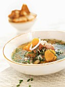Fish soup with carrots, onions and herbs