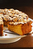 Mandarin cake with flaked almonds, sliced