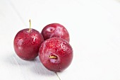 Red plums on a white surface