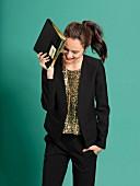 Junge Frau in schwarzer Hose mit Kurzblazer und Paillettentop