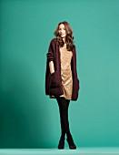 Junge Frau in Paillettenkleid und Cardigan im Oversize-Stil