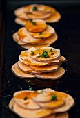 Stacks of sweet potato slices with fresh thyme