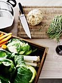 Frisches Gemüse, Rosmarin und Kochutensilien auf Küchenarbeitsplatte