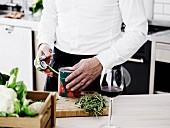 Mann öffnet mit Dosenöffner Konservendose in Küche