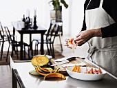 Mann in der Küche beim Zubereiten von Melone im Schinkenmantel